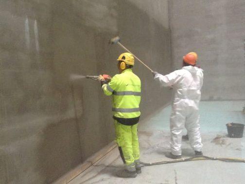 Workers preparing walls for waterproofing